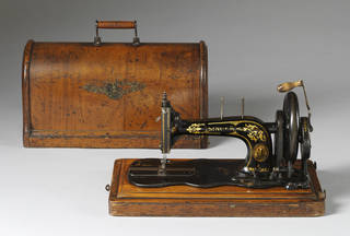 Cast iron, hand operated sewing machine. Painted black and is decorated in gold with an acanthus leaf pattern