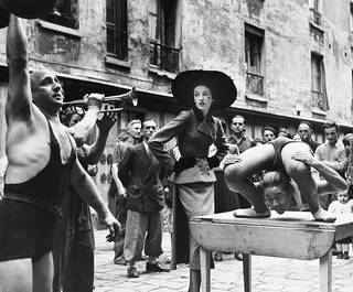 Elise Daniels with street performers, suit by Balenciaga, Le Marais, Paris, 1948. © The Richard Avedon Foundation