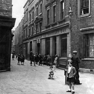Photo of street scene of Old Mahogany Bar, Graces Alley, about 1930. © Wilton's Music Hall
