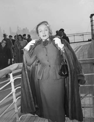 Marlene Dietrich wearing a suit by Christian Dior on the 'Queen Elizabeth' arriving in New York, 21 December 1950. © Getty Images