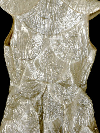 Coat completely covered in pale pink cellophane arranged in fan shaped motifs with graduated imitation pearls attached