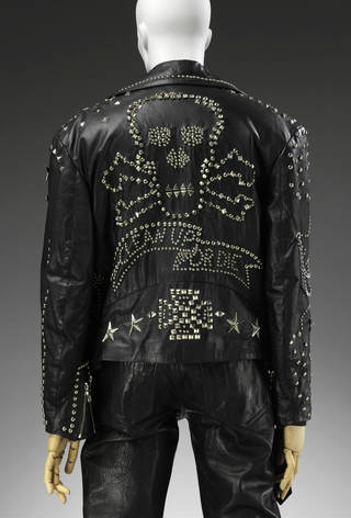 Black leather man's jacket with metal studwork of a skull and the words 'clean up or die'