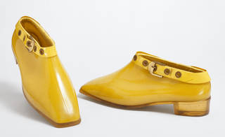 Pair of yellow PVC ankle boots with buckle around top