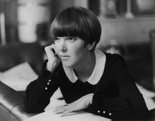 Black and white photo of Mary Quant sitting on a sofa with her hand on her cheek, looking into the distance