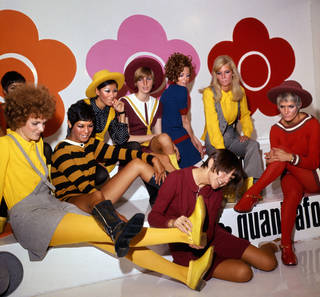 Photograph of Mary Quant and her models. She is holding a model's yellow shoe up