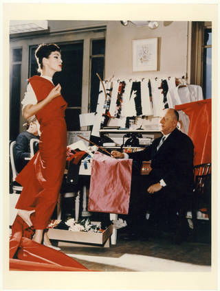 Photo of model Lucky having a red dress fitted. Christian Dior wears a black suit and sits at a table