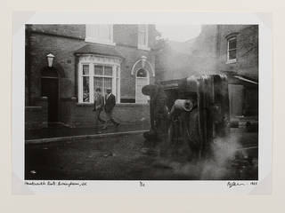 Underside of overturned car with two men walking past from the series Handsworth Riots, photograph by Pogus Caesar, 1985, England. Museum no. E.1200-2012. © Pogus Caesar/ Victoria and Albert Museum, London. Supported by the National Lottery through the Heritage Lottery Fund.