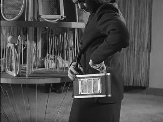 Still from 'Britain Can Make It No.12' (1946 Crown © / courtesy BFI), showing a woman demonstrating the portable 'handbag' radio.