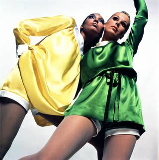 Model wearing yellow satin Quant dress and shorts, and model next to her wearing green satin Quant dress and shorts