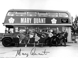 Black and white photo of Mary Quant branded London bus, with men and women posing outside it