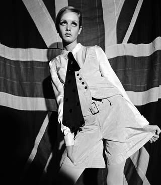 Black and white photo of Twiggy in front of a Union Jack flag, wearing a Mary Quant shirt, waistcoat, tie and shorts outfit