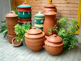 Several tall and short terracotta pots with lids. Some are painted green, red and yellow. Other are left natural