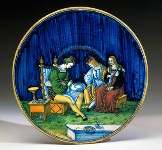 Maiolica plate showing a maiolica painter at work with two clients, Maestro Jacopo, about 1510 – 20, Italy. Museum no. 1717-1855. © Victoria and Albert Museum, London