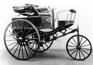 Early motorcar. Carriage suspended on a black structure with two side wheels and one smaller front wheel