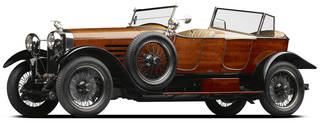 Brown motorcar with four wheels and spare wheel on the side. Headlights, and windscreen. Cream interior
