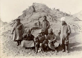 Group at Ulugh-mazar. Sir Aurel Stein in the centre with his dog Dash. © The British Library