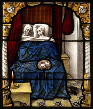 Stained glass panel depicting a man and woman in bed. The sheets are blue, and there is a dog at their feet