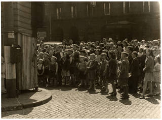 Audience standing to watch Professor Richard Codman lll's Punch and Judy booth outside Lime Street Station, Liverpool, about 1940, photograph by Waldo S. Lanchester. Museum no. S.3480-2013. © Victoria and Albert Museum, London