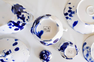 White plates, pots, and cups, with blue inky splat decoration