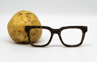 A potato with a pair of square framed glasses in front of it