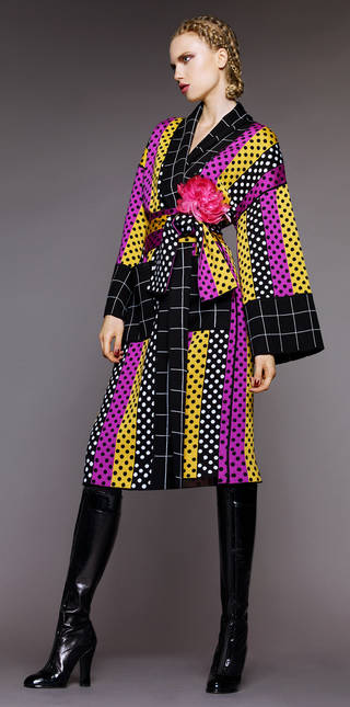 Model wearing a yellow, black and purple Kimono with polka dots inside the stripes and a flower at the waist