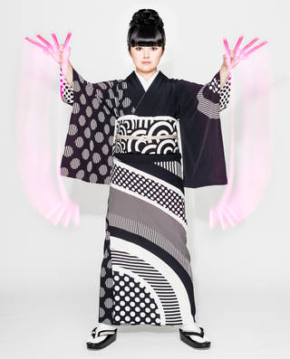 A woman wearing a black and white patterned Kimono. The patterns are polka dots and stripes