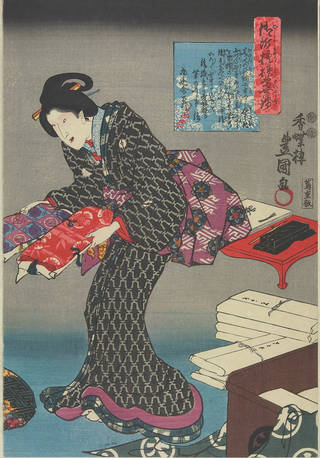 Woodblock print of a woman wearing a black and grey kimono. She holds a red fabric, and a blue and purple fabric