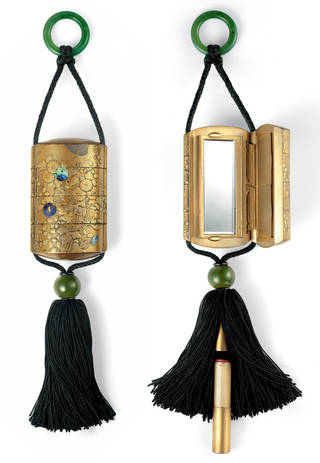 Two golden boxes with engraved flowers and black tassels at the bottom. They each open up to reveal a mirror inside