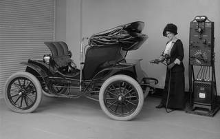 General Electric promotional photograph of a woman charging an electric car in her garage, about 1900. Image courtesy of miSci, Museum of Innovation & Science