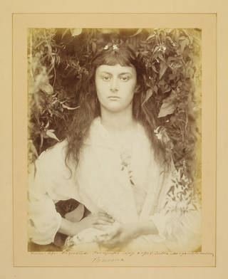 Sepia-toned portrait of a woman with hand on hip, surrounded by foliage
