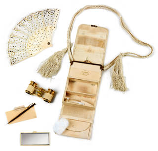 Cream handbag with a rope handle, opened up. Contents include a fan, binoculars, a mirror, and a pen.