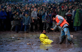 A festival-goer defeated by the mud, 1990s. © Ann Cook