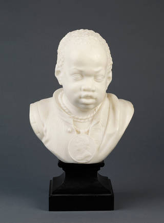 White marble bust of a young black boy, wearing a medallion around his neck.