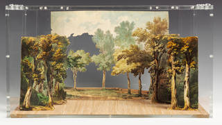 Paper set model with a blue sky, and autumnal looking green and orange trees to the left, right and back.