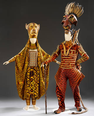 Two costumes. One of a yellow lion face on a hat, with bright yellow and brown patterned robes. The other is a brown lion face with green eyes and spiky hair, and orange and black patterned robes.