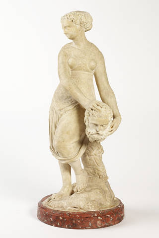Creamy white stone statue of Judith, holding the head of Holofernes by her hip