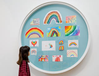 Child looking at a round frame containing rainbow artworks by children