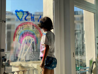 Girl looking out a window with an NHS rainbow drawn onto it