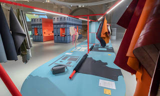View of the Bags exhibition featuring a blue table in the foreground and swatches of orange and red material hanging up.