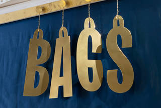 Gold letters that spell BAGS hanging on a blue fabric background