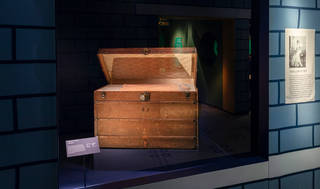 Brown trunk with the lid ajar on display behind glass with a blue brick effect surround.