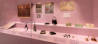 Pink coloured display case with bags on plinths and 2D material on the back wall