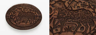 Brown oval shaped piece of wood with a sheep and leaf patterns engraved in it.