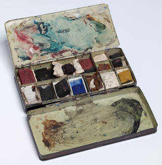 Open paintbox with dry lumps of paint in compartments and swirls of dried and smudged paint in the tray and lid.