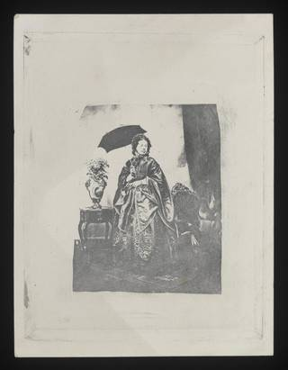 Studio portrait of a woman standing with a black parasol'