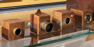 Four simple box 'mousetrap' cameras that belonged to Fox Talbot with different sized lenses. Browns and yellows.