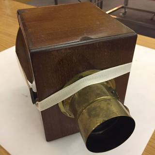 Brown wooden box camera with brass lens at the front.
