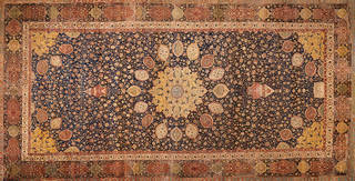 Large intricately patterned carpet in blue, burnt orange, and yellow tones. Decorative circular pattern moving out from middle.