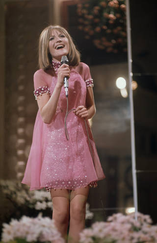 Sandie Shaw singing at Eurovision, wearing the pink sparkly dress. It is light pink and has a darker pink and white beading around the collar, sleeves and hem.