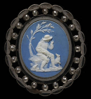 Oval brooch of cut and polished steel, and mounted with a plaque of blue jasper-dip with a white cameo depicting a shepherd boy seated under a tree with a lamb in his arms and a dog at his feet.